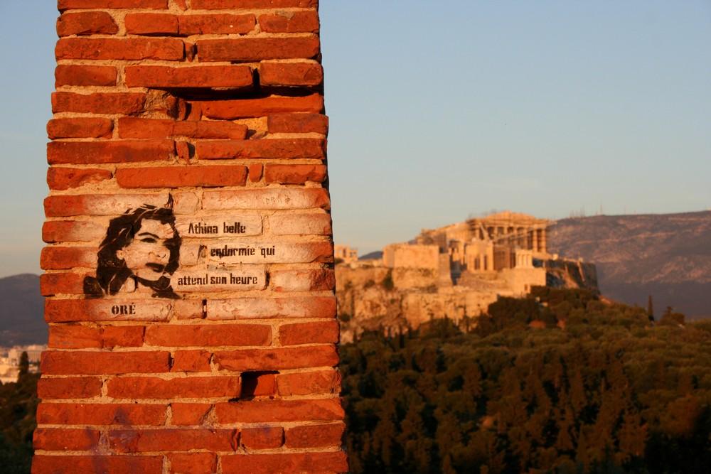 Athen_Streetart_von_Oré. Im Hintergrund der Akropolishügel